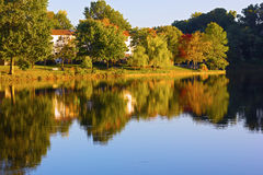 Autumn in a front lake community of Northern Virginia, US. Picturesque residential neighborhood with colorful trees in the fall Royalty Free Stock Photography