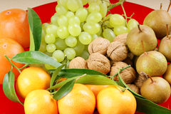 Autumn fruits. Assortment of autumn fruits on a red plate Royalty Free Stock Photos