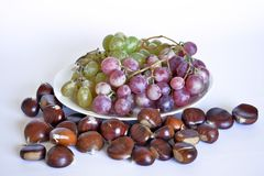Autumn fruits, chestnuts and grapes. Composition with chestnuts and grapes, dried leaves, white background Stock Photo