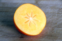 Autumn fruits: half persimmon on a chopping board Royalty Free Stock Image