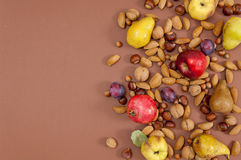 Autumn fruits and nuts on brown background with copy space Royalty Free Stock Images