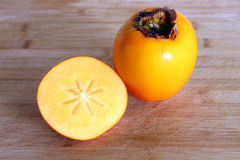Autumn fruits: one persimmon and half Royalty Free Stock Images