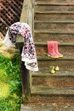 Autumn fruits on a vintage old wooden staircase. Autumn mood, warm clothes. Life style. Porch of the old house. Red Rubber boots stock photography
