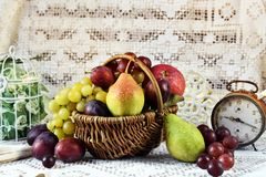Autumn fruits in vicker basket. Autumn fruits in wicker basket on the table in vintage style interior stock photos