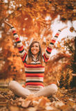 Autumn Fun. Cute young woman enjoying in sunny forest in autumn colors. She is sitting on the ground covered with leaves and having fun Royalty Free Stock Photography