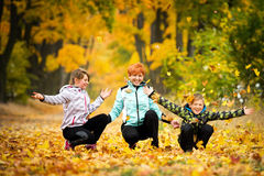 Autumn fun. Mother playing with children in the park in autumn Royalty Free Stock Image