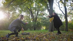 Autumn fun, two smiling women and little funny girl playing in the park, rushing leaves at each other while relaxing