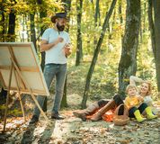 Autumn garden party - Father, mather and son. Camping with kids. Enjoying good weather. Man artist painting autumn. Picture royalty free stock photos