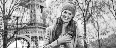 Smiling young elegant woman near Eiffel tower with cellphone. Autumn getaways in Paris. Portrait of smiling young elegant woman near Eiffel tower with cellphone Stock Images