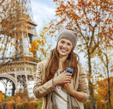 Smiling young elegant woman near Eiffel tower with cellphone Royalty Free Stock Photography