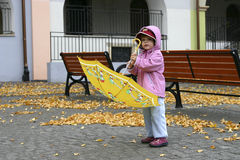 Autumn girl. Little girl playing with a yellow umbrella Stock Images