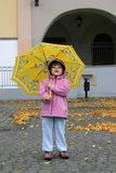 Autumn girl. Little girl playing with a yellow umbrella Royalty Free Stock Image