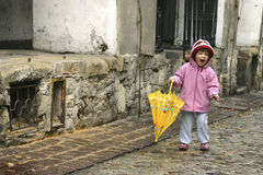 Autumn girl. Little girl playing with a yellow umbrella Stock Photography