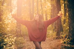 Autumn girl. Autumnal mood. Female autumn fashion concept. Freedom Concept. Beautiful young happy girl with a bright red. Yellow leaf in the park. Yellow Trees royalty free stock image