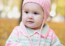 Autumn girl. Baby girl in a pink cap walks in autumn park stock photography