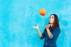Autumn Girl in der Denim-Ausstattung, die mit einem Kürbis spielt lizenzfreie stockfotos