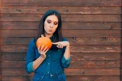 Autumn Girl die in Denimuitrusting een Pompoen houden royalty-vrije stock afbeeldingen