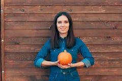 Autumn Girl die in Denimuitrusting een Pompoen houden stock afbeeldingen