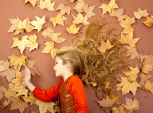 Autumn girl on dried leaves Stock Photos