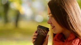 Autumn Girl Drinking Coffee Fall-Konzept der jungen Frau heißes Getränk von der Wegwerfkaffeetasse im Fall-Park genießend stock footage