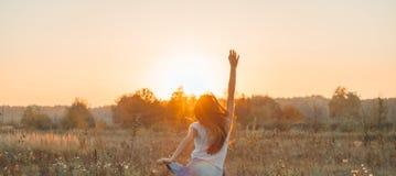 Autumn Girl enjoying nature on the field. Beauty Girl Outdoors raising hands in sunlight rays. Beautiful Teenage Model girl. In white dress running on the Field stock photos