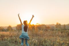 Autumn Girl enjoying nature on the field. Beauty Girl Outdoors raising hands in sunlight rays. Beautiful Teenage Model girl. In white dress running on the Field stock image