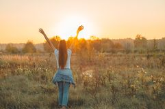 Autumn Girl enjoying nature on the field. Beauty Girl Outdoors raising hands in sunlight rays. Beautiful Teenage Model girl. In white dress running on the Field royalty free stock images