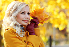 Autumn Girl. Fashion Blonde Beautiful Woman with Maple leaves. In hand. Fall park Stock Images