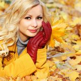 Autumn Girl. Fashion Blonde Beautiful Woman with Maple leaves in. Hand. Looking at camera. Fall park Stock Photography