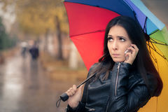 Autumn Girl Holding a Rainbow Umbrella and a Smartphone Stock Photos