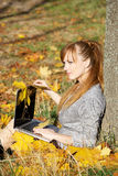 Autumn girl with laptop. Young woman in autumn park with laptop Stock Images