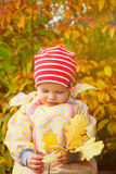 Autumn girl. Little baby girl outdoors discovers autumn leaves Stock Image