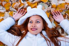 Autumn girl playing in city park. Portrait of an autumn woman lying over leaves and smiling outside in fall forest. Beautiful ener Royalty Free Stock Photos