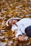 Autumn girl playing in city park. Portrait of an autumn woman lying over leaves and smiling outside in fall forest. Beautiful ener stock photos