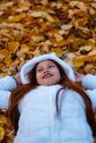 Autumn girl playing in city park. Portrait of an autumn woman lying over leaves and smiling outside in fall forest. Beautiful ener Stock Photography