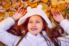 Autumn girl playing in city park. Portrait of an autumn woman lying over leaves and smiling outside in fall forest. Beautiful ener Stock Photo