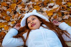 Autumn girl playing in city park. Portrait of an autumn woman lying over leaves and smiling outside in fall forest. Beautiful ener royalty free stock images