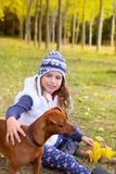 Autumn girl in poplar tree forest playing with dog Stock Photo