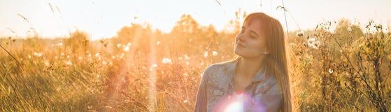 Autumn Girl que disfruta de la naturaleza en el campo La muchacha de la belleza al aire libre que aumenta las manos en luz del so fotografía de archivo