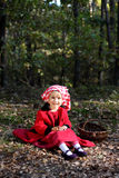 Autumn girl in a red scarf. The little girl in a red cap in the autumn forest Stock Photos