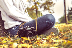 Autumn, girl sitting in a park with camera Royalty Free Stock Photos