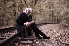 Autumn girl sitting on rails. Young beautiful woman sitting on rails in autumn scenery. Concept of an autumn mood Stock Images