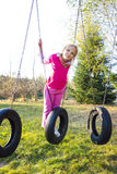 Autumn Girl on Swing. Girl in pink swinging on a tire swing at the park stock photos