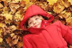 Autumn - the girl is in the yellow leaves Royalty Free Stock Image