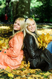 Autumn girls. Cute girls sitting on leaves Royalty Free Stock Photos