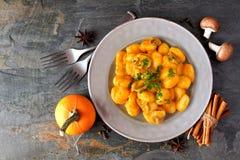Autumn gnocchi with pumpkin cream sauce, top view table scene over slate Stock Photos