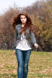 Autumn go. Beautiful young woman in autumn park Royalty Free Stock Photos