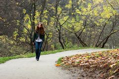 Autumn go. Beautiful young woman in autumn park Stock Photography