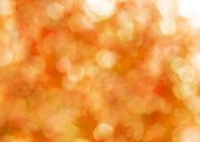 Autumn gold abstract background, blurred sun light. Bokeh. Orange, brown and yellow dots royalty free stock photography