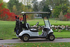 Autumn golfcart. Caddy golfcart by the field in the autumn Royalty Free Stock Photos